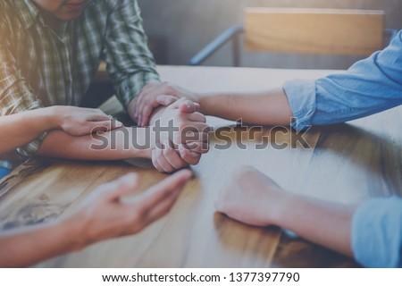 Two Christian people are praying for young man friends on wood table at church prayer room to encourage and support him in his problem and spiritual growth, small prayer group and fellowship concept