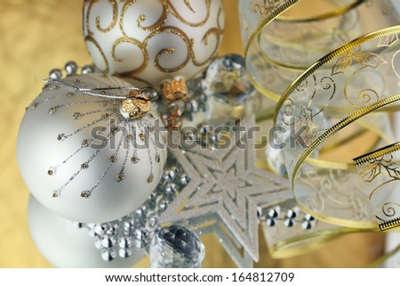 Two Christmas baubles, cristal sphere, star and ribbon on golden background with reflections
