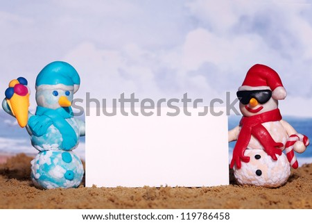 Two christmas snowmen with billboard on sea beach