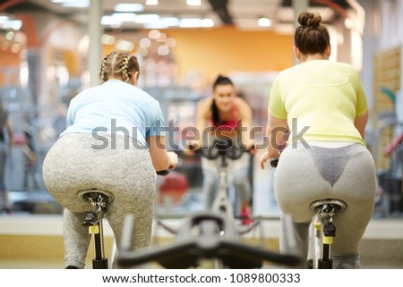 Two chubby young women in activewear cycling on bikes in front of their trainer in gym