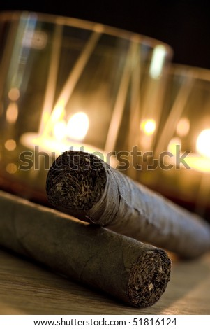 Two cigars in warm light from two candles in the background.