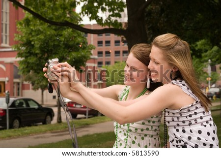 Two city teens smiling as they take self-portrait with a point-and-shoot camera.