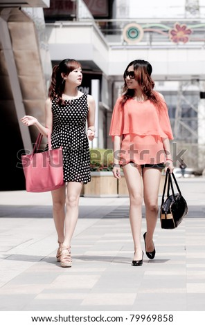 two city young women walking with bag  in the street
