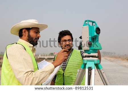 two civil engineers doing a survey on a construction site. Engineers doing land survey at a construction site
