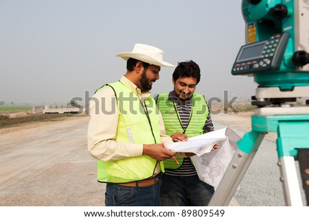two civil engineers doing a survey on a construction site. engineers doing land survey on site.