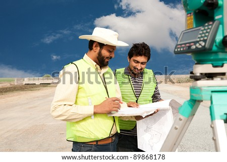 two civil engineers doing land survey at a construction site