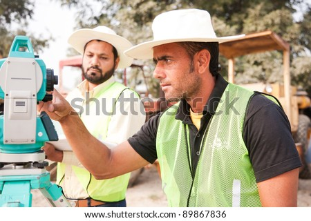 two civil engineers doing land survey at a construction site with construction machinery in the background