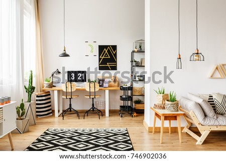 Shutterstock Two classic chairs at table with laptop and lamp in scandinavian style workspace with pillows on sofa