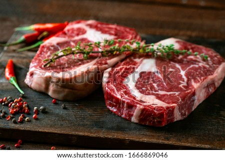 Two classic fresh rib eye steaks on a wooden Board