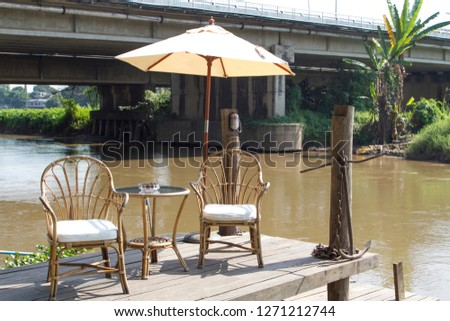 Two classic vintage chairs, table and white umbrella near river #1271212744