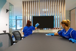 Two cleaners with masks on their faces are cleaning the office photo