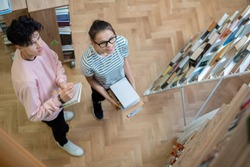Two clever teenage students in casualwear looking at one of bookshelves in college library while going to prepare for seminar