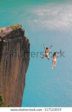 two cliff jumping girls, against turquoise ocean ストックフォト ©