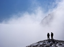 Two climber silhouettes in mountains covered in fog