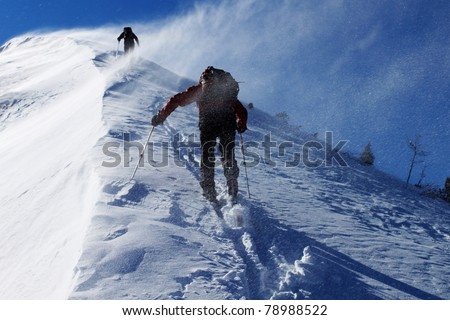 Two climbers ascending snow ridge in snow storm