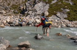 Two climbers crossing the glacier river Electrico, on their way to the glacier Marconi, Los Glaciares National Park, Argentina.