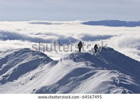 two climbers on a mountain top in winter, Piatra Craiului Mountains, Romania