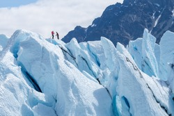 Two climbers reached the top of glacier. Challenging and hostile environment. Several crevices around. Matanuska glacier, Alaska, USA / Two climbers reached the top of glacier