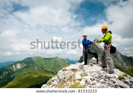 two climbers shake hands on the summit to celebrate success
