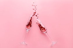 Two clinking champagne glasses with splash of red heart shaped confetti over pink background. Overhead view, copy space. Valentine's Day concept