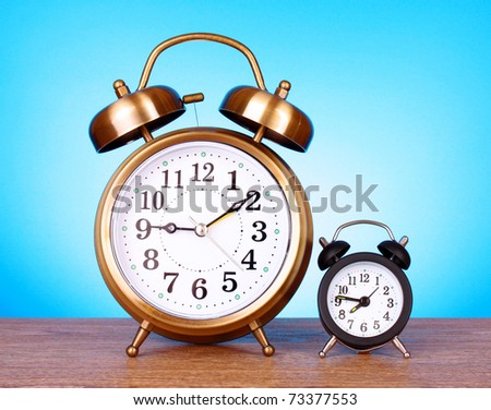 Two clocks with different time on blue background