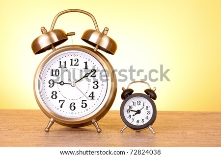 Two clocks with different time on yellow background