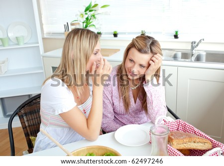 Two close female friends talking together in the kitchen at home