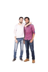 Two close friends standing, taking a photo, one of them his arm around his friend's neck, smiling, isolated on a white background.