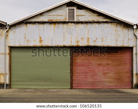 Two closed painted green and red garage doors in the front of an old corrugated iron building with weathered rusting facade