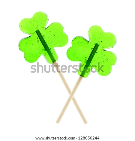 Two clover leaf shaped St Patrick's Day lollipops isolated on white