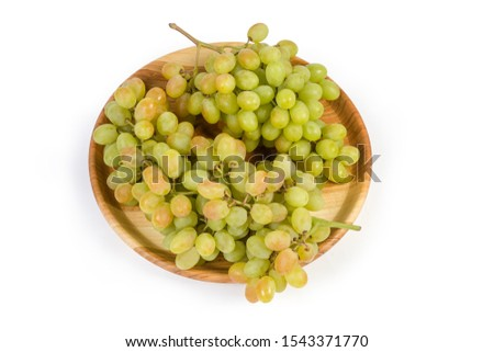 Two clusters of the ripe white sultana grapes on vintage wooden dish on a white background