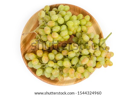 Two clusters of the ripe white sultana grapes on vintage wooden dish on a white background, top view
