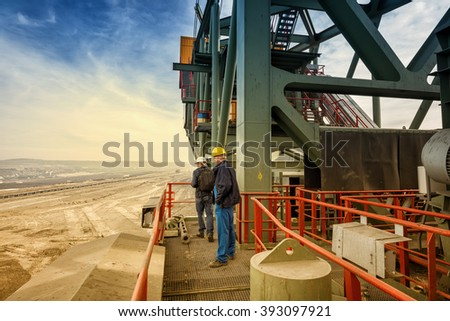 Two coal mine engineers with protective helmets standing on a huge drill machine, talking and watching at the digging site. Beautiful and colorful sky in the background. Rear view.