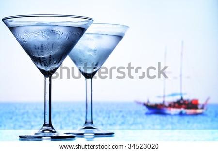 Two cocktail glasses and sea in the background