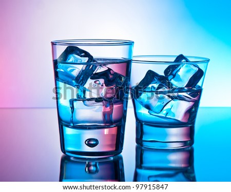 Two cocktails on the rocks on a reflective surface