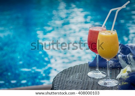 Two cocktails red and yellow on table against blue swimming pool. Travel, luxury, vacation background. Detox healthy drink. Text space