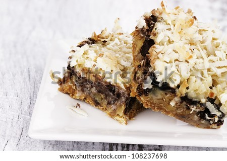 Two coconut chocolate chip bars over a rustic background. Shallow depth of field.