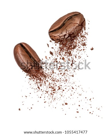 Two coffee beans broken into powder close-up on a white background