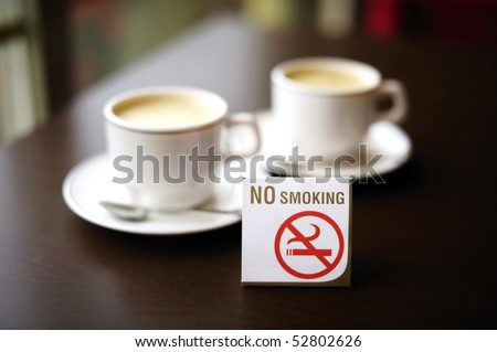 Two coffee cups and a no smoking sign