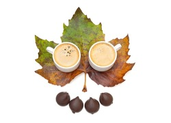 Two coffee cups and chocolate candies on a large pigmented maple leaf isolated on white