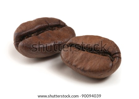 two coffee grains on white background