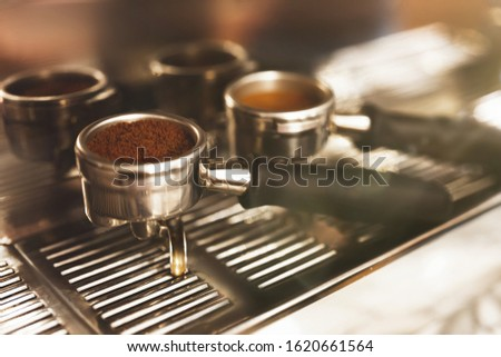 two coffee holders one with ground coffee near professional coffee machine close up, barista tools.