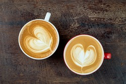 Two coffee or latte art heart shape  in a coffee cup on wooden table