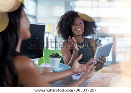 Two  colleages discussing ideas using a tablet and computer