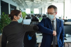 Two colleagues avoid a handshake when meeting in the office and greet bumping elbows. Greetings in Wuhan. A man and a woman in medical masks maintain a social distance at work.