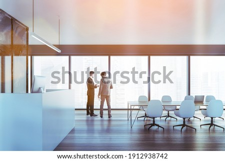 Two colleagues discussing clients business case before the meeting in modern panoramic office in downtown. reception area and fulllengthwindows. Lens flare Photo stock ©