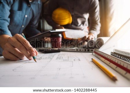 Two colleagues discussing data working and tablet, laptop with architectural project at construction site at desk in office #1402288445