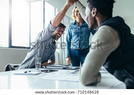 Two colleagues giving high five in meeting. Business people celebrating success in conference room.