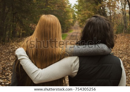 Two college age girls in the woods with a path ahead of them with arms around each other. Season is fall.  Stock photo ©