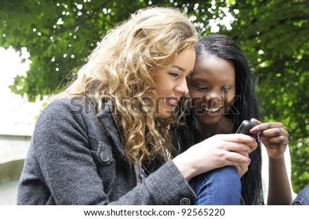 Two college friends smiling while reading a text message on a mobile phone.